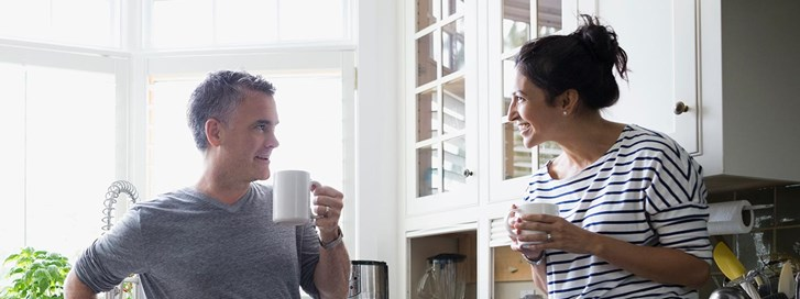 Couple drinking coffee in their kitchen while discussing UW Credit Union's rapid refinance services