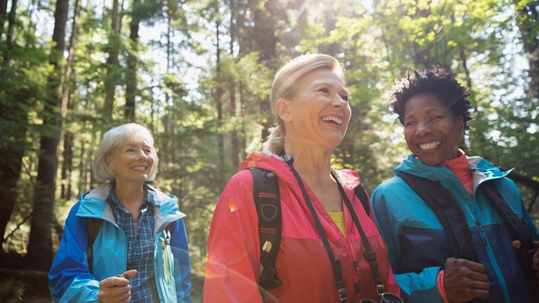 Senior women discuss savings and investments while hiking outdoors