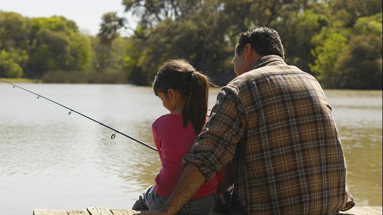 A parent and child fishing on a lake in a serene and peaceful setting