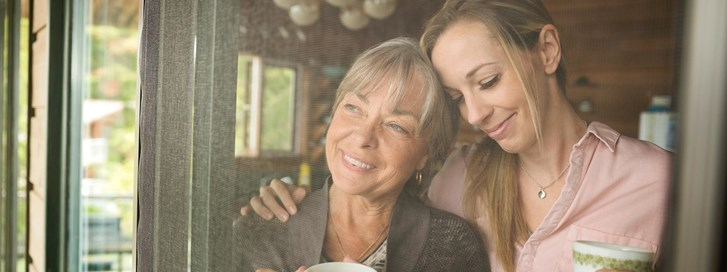 Mother and daughter drink coffee and discuss saving money with UW Credit Union