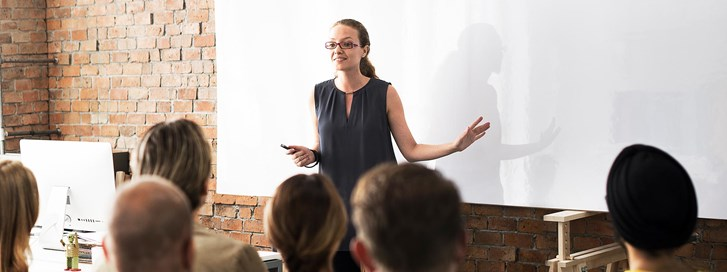 Woman delivering a financial seminar to an audience