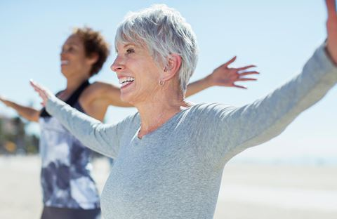 Two smiling women stretching their arms