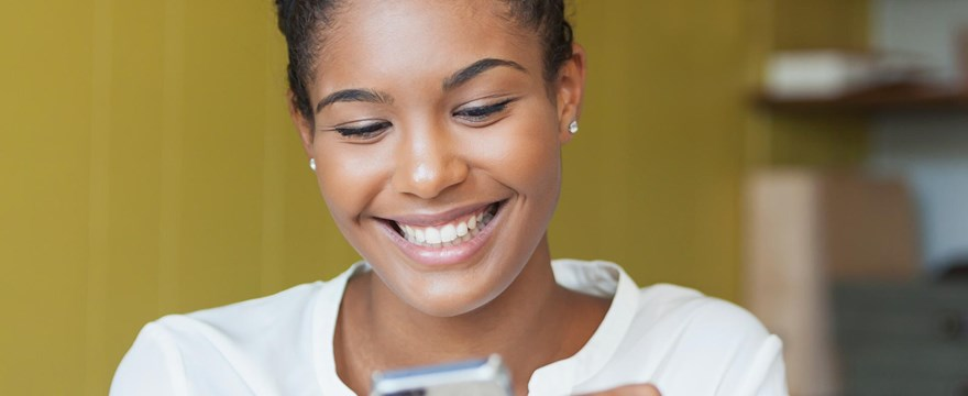 Young woman smiles while using her mobile device