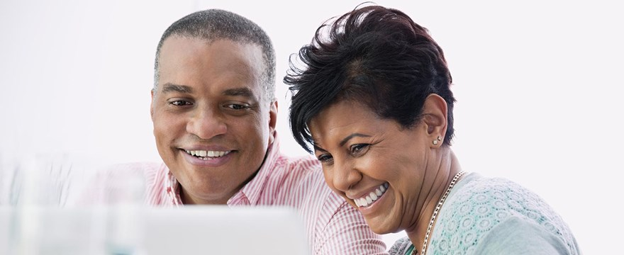 Man and woman smile while looking at a computer screen
