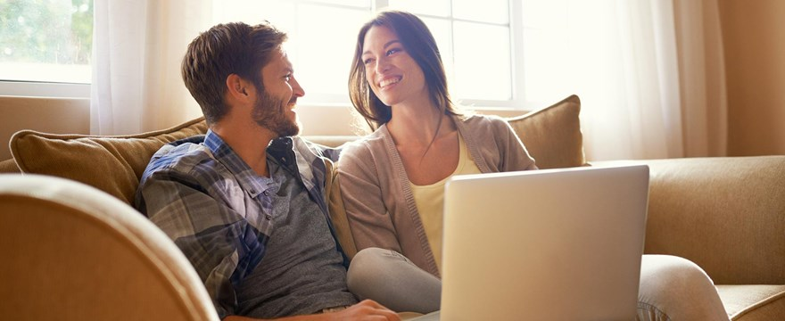 Couple sits together on the couch to discuss financial planning