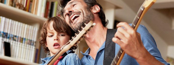 Father and son play guitar together in their new home.