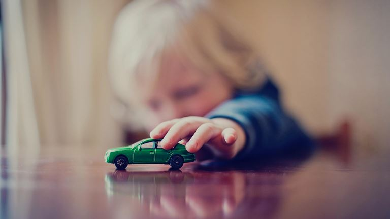 Child plays with a toy car.