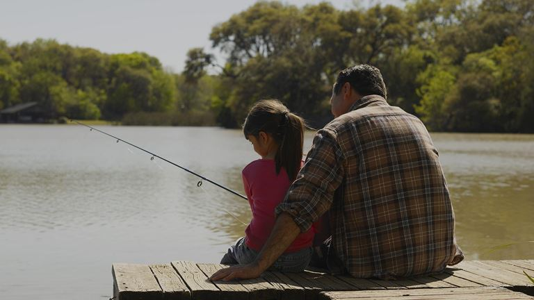 Man and child sit on a dock with a fishing pole.