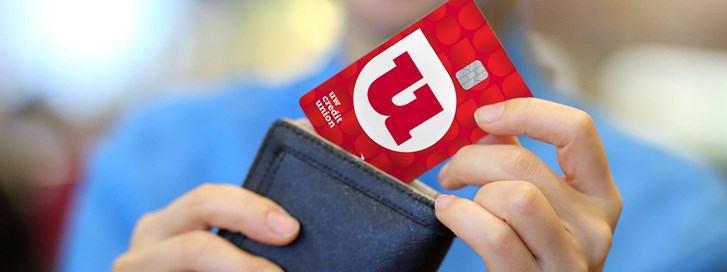 Woman putting her new UW Credit Union Credit Card in her wallet