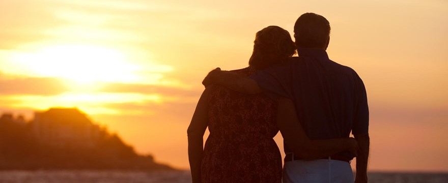 Couple stands on the beach at sunset.