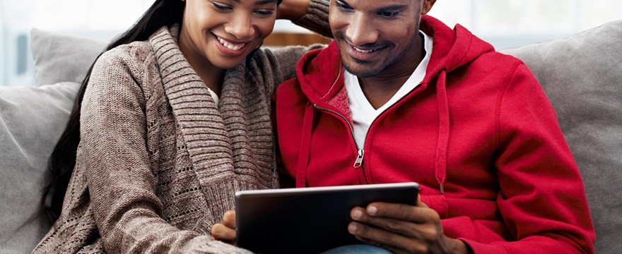Couple sits on a couch looking at finances on a tablet.