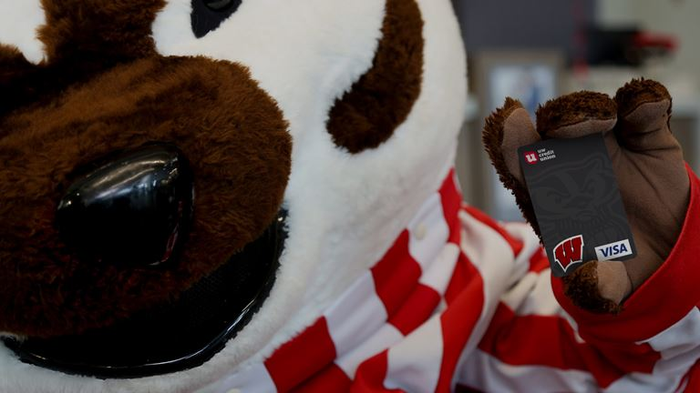 Bucky Badger holding his very own Bucky Credit Card from UW Credit Union.