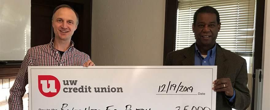 Vincent Noth accepts a check for $25,000 from UWCU's Jaimes Johnson.