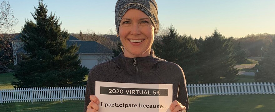 "A woman stands outside on a deck holding a sign for the Virtual 5K. The sign reads ""I participate because I want to give back -- I have more than I need."""